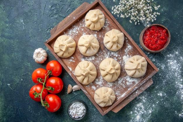 Vista dall'alto gnocchi crudi con carne e pomodori sulla superficie scura farina colore farina piatto pasta di cottura della carne