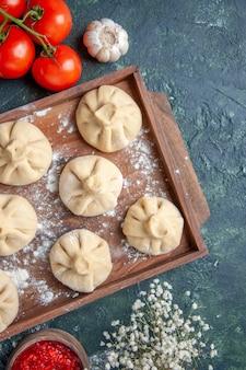Vista dall'alto gnocchi crudi con carne e pomodori sulla superficie scura farina colore farina pasta cottura della carne