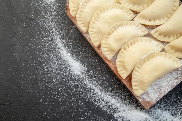 어두운 배경에 밀가루 으깬 감자와 계란을 넣은 원시 작은 핫케이크 파이 반죽 굽기 요리 비스킷 오븐 케이크 음식