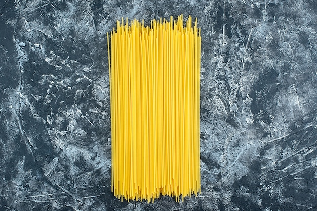 Top view raw long pasta on the gray background kitchen pasta dough kitchen cuisine color food cooking