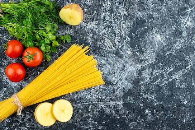 밝은 회색 배경 주방 파스타 반죽 음식 요리 주방 색상 요리에 녹색과 토마토를 곁들인 원시 긴 파스타