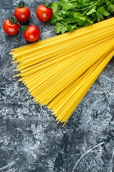 Top view raw long pasta with greens and tomatoes on a gray background color kitchen pasta dough food cooking kitchen cuisine