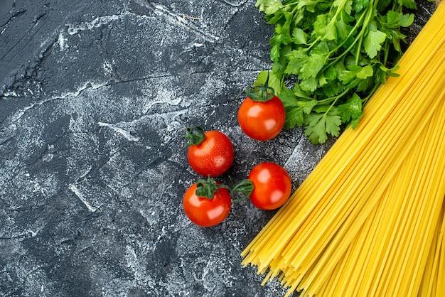 Vista dall'alto pasta lunga cruda con verdure e pomodori su sfondo grigio colore cucina pasta pasta cibo cucina cucina