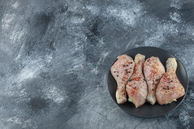 Vista dall'alto di cosce di pollo marinate crude su sfondo grigio.