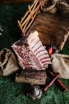 Top view raw meat ribs on a tray with a bottle of red wine burlap bags on the grass