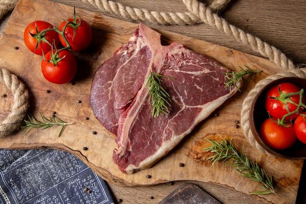 Вид сверху кусок сырого мяса со свежими красными помидорами и зеленью на деревянном фоне