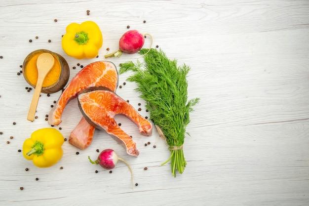 Fette di carne cruda vista dall'alto con verdure e peperoni su sfondo bianco