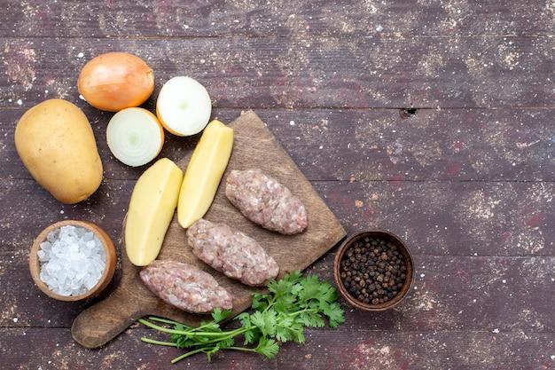 Вид сверху сырое мясо с сырым картофелем, соленый лук, блокнот и зелень на коричневом фоне, блюдо из мяса и картофеля, ужин