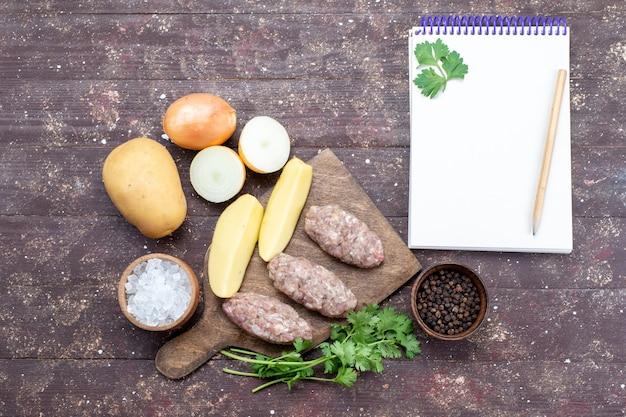Вид сверху сырое мясо с сырым картофелем, соленый лук, блокнот и зелень на коричневом столе, мясо, картофельное блюдо, ужин