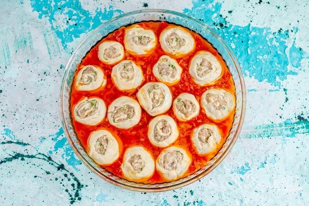 上面図生の肉生地のスライス、ひき肉、トマトソース、ガラス鍋、青いテーブルフードミール生地肉ディナー