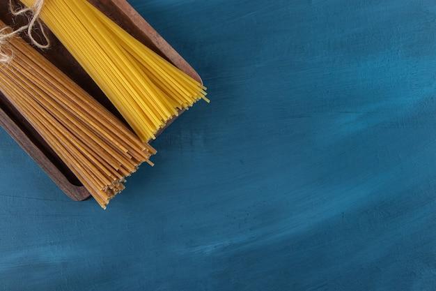 Vista dall'alto di noodles crudi su sfondo blu scuro.