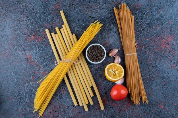 Vista dall'alto di noodles crudi con pomodori rossi freschi e aglio su una superficie scura.