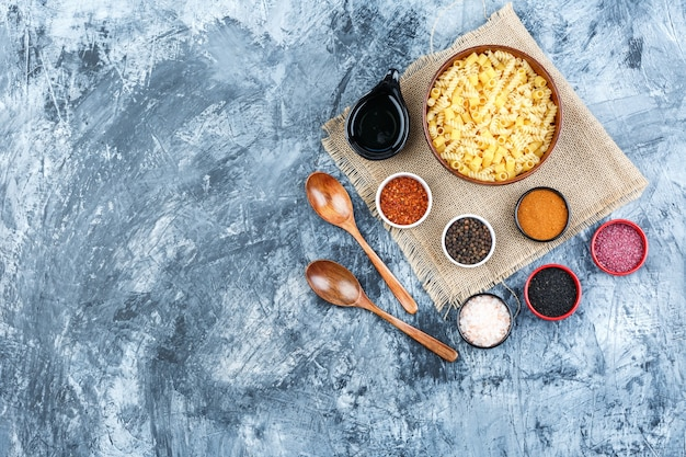 Top view raw pasta in bowl with spices, scoop, wooden spoons on plaster and piece of sack background. horizontal