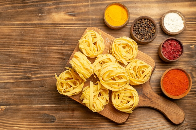 Top view raw pasta designed pasta with different seasonings on brown wooden background dough meal food pasta