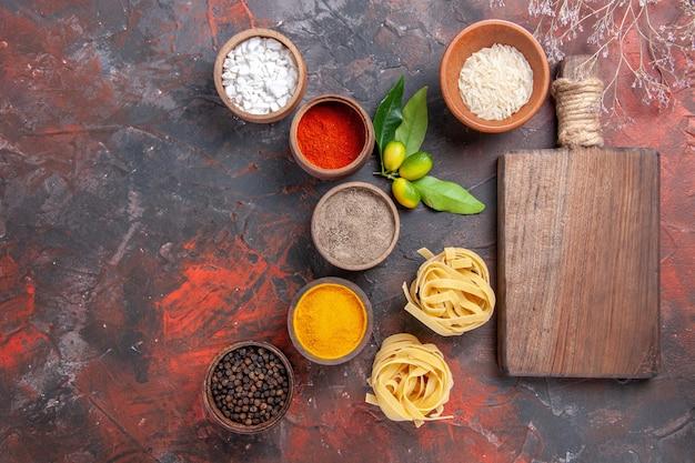 Vista dall'alto di pasta cruda diversi condimenti sulla pasta cruda superficie scura