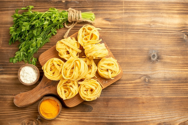 茶色の背景に調味料と緑の生パスタ生地の上面図生地ミールフードパスタ