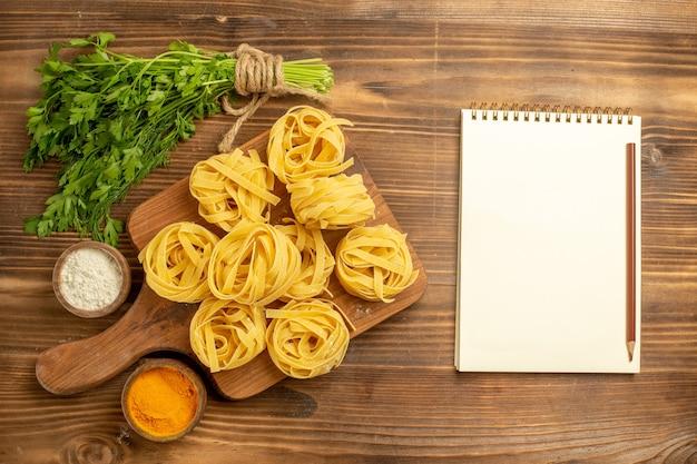 Vista dall'alto impasto di pasta cruda con condimenti e verdure sulla pasta alimentare farina di sfondo marrone