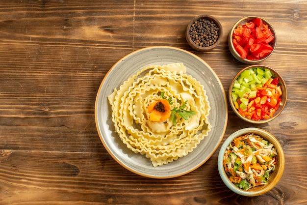Vista dall'alto impasto di pasta cruda con condimenti e verdure su sfondo marrone pasta pasto cibo crudo pasta