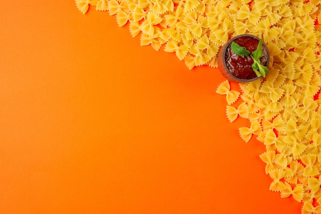 Top view of raw pasta farfalle with ketchup in a saucepan and copy space on orange