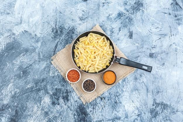 石膏と袋の背景にスパイスが入った鍋のトップビュー生パスタ。水平
