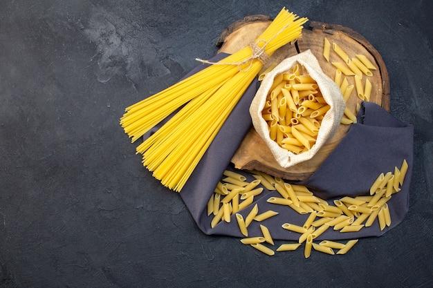 Вид сверху сырые макароны длинные и маленькие на темном фоне еда макароны ужин еда готовка кухня темнота