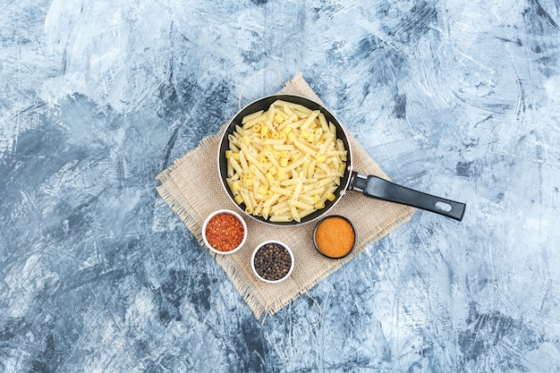 Top view raw pasta in pan with spices on plaster and piece of sack background. horizontal