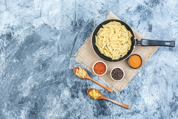 Top view raw pasta in pan and wooden spoons with spices on plaster and piece of sack background. horizontal