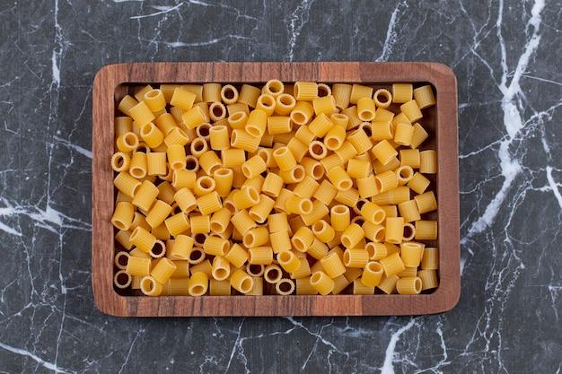 Penne di pasta cruda vista dall'alto sul piatto di legno.