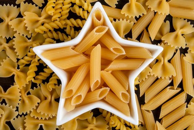 Vista dall'alto di pasta cruda in una coccarda a forma di stella con spaghetti su una superficie di legno