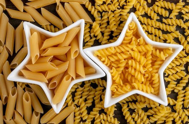 Vista dall'alto di pasta cruda in rosetta a forma di stella su una superficie di legno