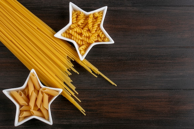 Top view of raw pasta in star shaped saucers with raw spaghetti on a wooden surface