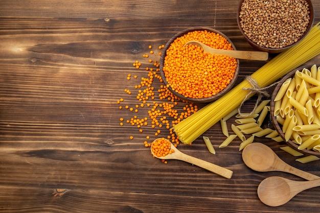 Vista dall'alto pasta cruda con grano saraceno e lenticchie su superficie marrone
