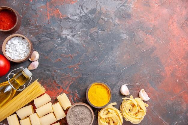 Vista dall'alto pasta cruda con diversi ingredienti sull'impasto per pasta di colore superficie scura