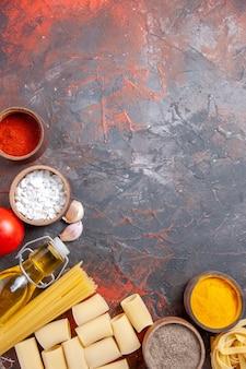 暗い表面の色のパスタ生地にさまざまな成分を含む上面の生パスタ