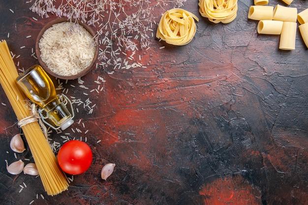 Вид сверху сырых макарон с разными ингредиентами на темной поверхности цветного теста для макарон