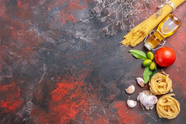 Вид сверху сырой пасты с маслом и помидорами на темной поверхности теста сырой пасты