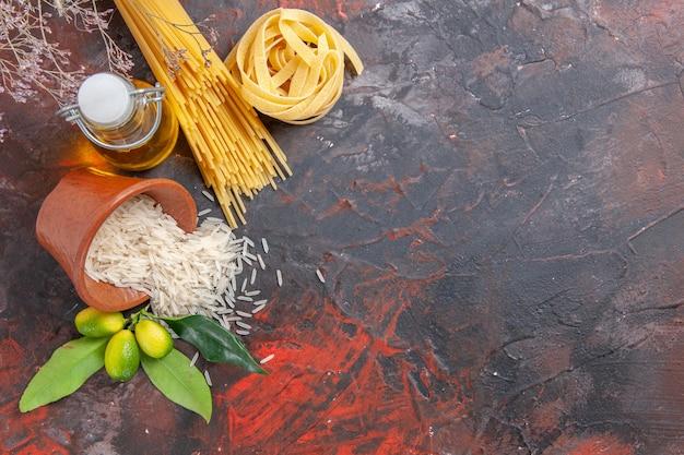 Vista dall'alto di pasta cruda con olio e riso su una pasta di pasta cruda superficie scura