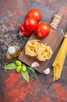 어두운 바닥 원시 파스타 반죽에 기름 토마토와 마늘 상위 뷰 원시 파스타 무료 사진