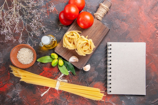 Vista dall'alto di pasta cruda con olio e pomodori su pasta cruda superficie scura