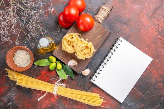 Vista dall'alto pasta cruda con pomodori olio e aglio su pasta cruda superficie scura