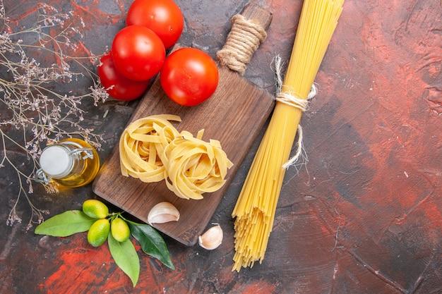 Vista dall'alto di pasta cruda con pomodori olio e aglio su pasta di pasta cruda superficie scura