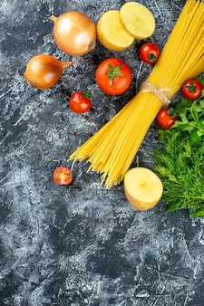 Top view of raw pasta with potato, parsley and tomatoes on light gray surface