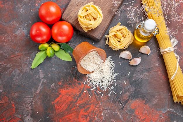 어두운 표면 파스타 반죽에 쌀과 빨간 토마토와 상위 뷰 원시 파스타