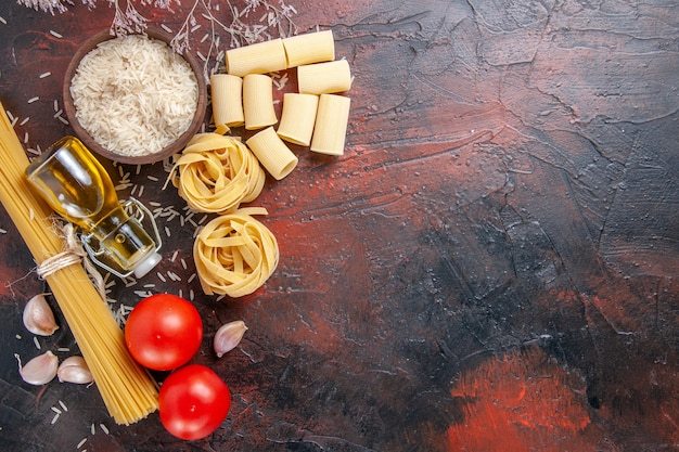 Top view raw pasta with rice and tomatoes on a dark surface dough pasta raw