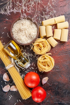Vista dall'alto pasta cruda con riso e pomodori sulla pasta di pasta superficie scura cruda