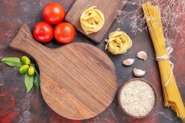 Vista dall'alto di pasta cruda con riso e pomodori sull'impasto di pasta superficie scura cruda