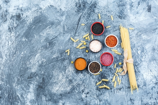 Top view raw pasta with spices on grey plaster background. horizontal
