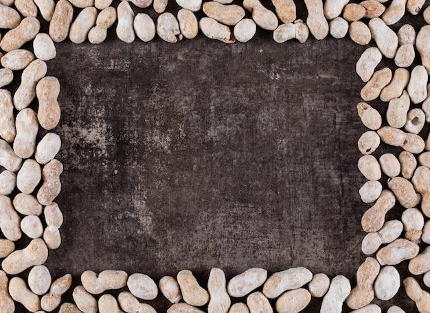 Cornice di arachidi crudo vista dall'alto con spazio di copia al centro sul buio