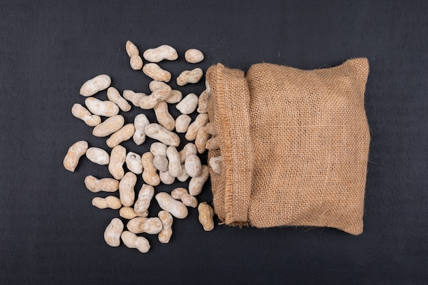 Top view raw peanuts in sack on dark