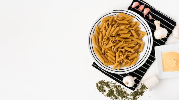 Top view of raw penne pasta and it's ingredients on white backdrop
